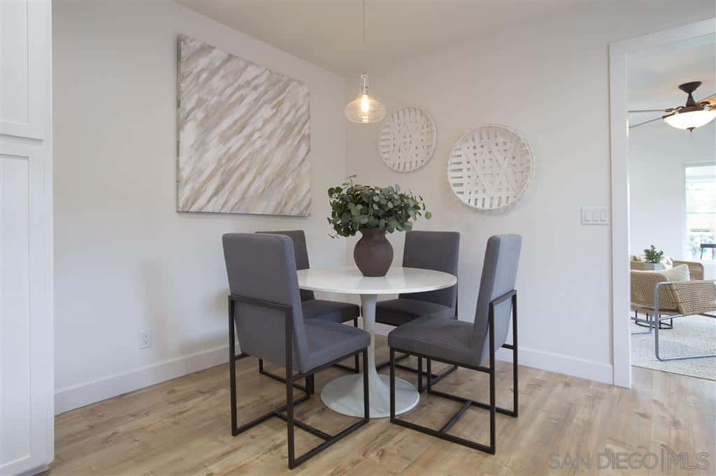 This is a small corner dining room that has a white ceiling and white walls that are adorned with wall-mounted artworks that are a different shade of white for that monochromatic effect. This is augmented by the white circular table and hanging pendant light. The contrast in this room is the modern cushioned chairs around the table.