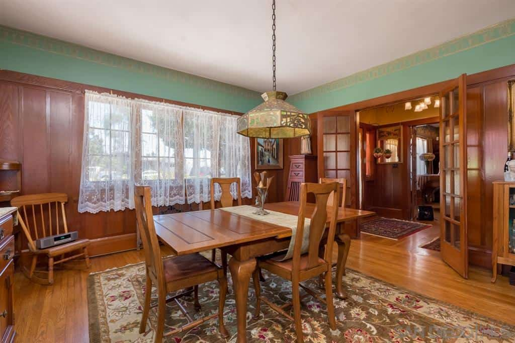 The upper walls have a greenish tinge that serves as a good mediator for the white ceiling and wooden finish of the walls that match with the hardwood flooring. The flooring is topped with a greenish floral-patterned area rug that contrasts the wooden table and fiddleback chairs.