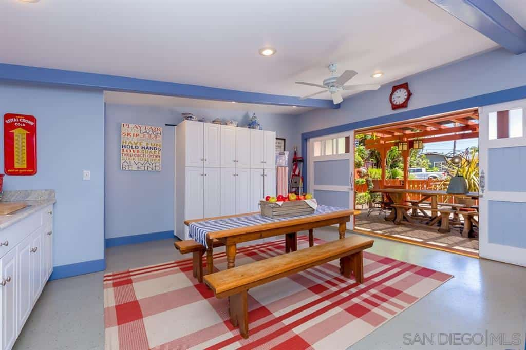 The colors and vibrancy of this Craftsman-Style dining room amp the quality of warmth. The walls and ceiling are given hues of blue that makes the white ceiling and white checkered area rug pop out. This also affects the wooden table and the benches that flank it.