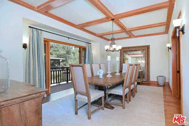 This Craftsman-Style dining room is dominated by white hues and wooden elements. The white ceiling has exposed wooden beams that mirror with the frame of the French doors white the dining table and chairs has the same material as the frame of the mirror leaning on a wall.