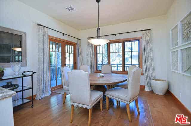 The hardwood flooring of this dining room seems to extend to the frames of the glass door and windows. Amongst these, the wooden round table in the middle room stands out because of the leather dining chairs surrounding it. The airy quality is brought by the glass door and windows.