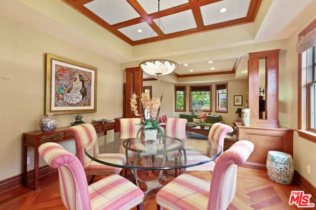 This Craftsman-Style dining room has a chic personality to it due to the striped cushioned of the Parsons chairs surrounding the glass-top round table. There is an amazing wall-mounted artwork that hangs over the console table that matches well with the hardwood floor and exposed beams of the ceiling.