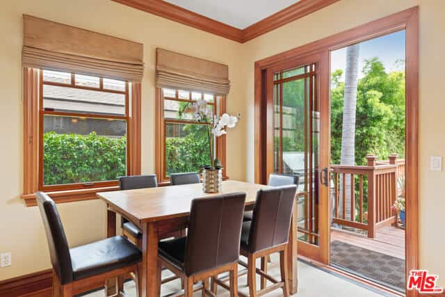 Leather Parsons chairs encircle the wooden dining room that pairs well with the frames of the windows and glass sliding doors that lead to the outdoors. This gives a sense of space to this intimate dining area and further enhanced by the white area rug over the hardwood flooring.