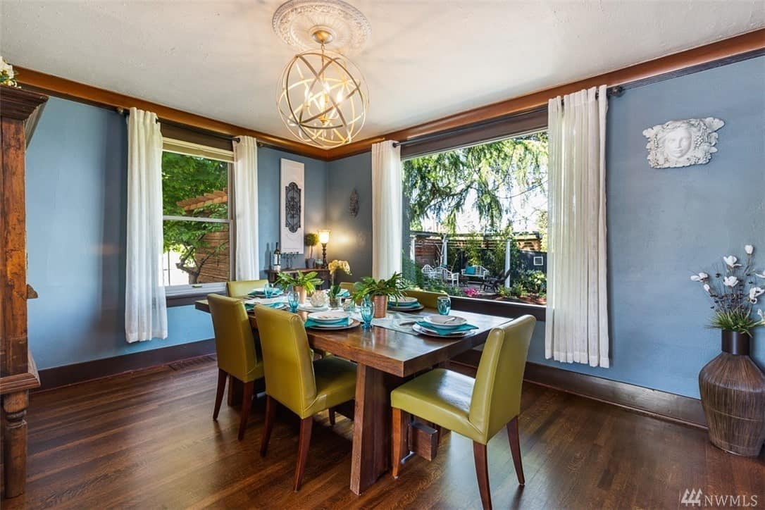 This Craftsman-Style dining area has lovely bluish walls that mediate perfectly between the white ceiling and hardwood floors that match the wooden table. Surrounding the table are avocado-colored leather chairs that are illuminated by the natural light of the windows and yellow light of the modern spherical chandelier.