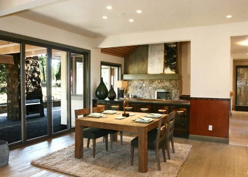 The heavy wooden table of this dining room stands over a woven area rug with a furry texture that contrasts the smooth hardwood floor. Glass doors and windows provide illumination for the dark wooden tones and neutralize them at the same time.