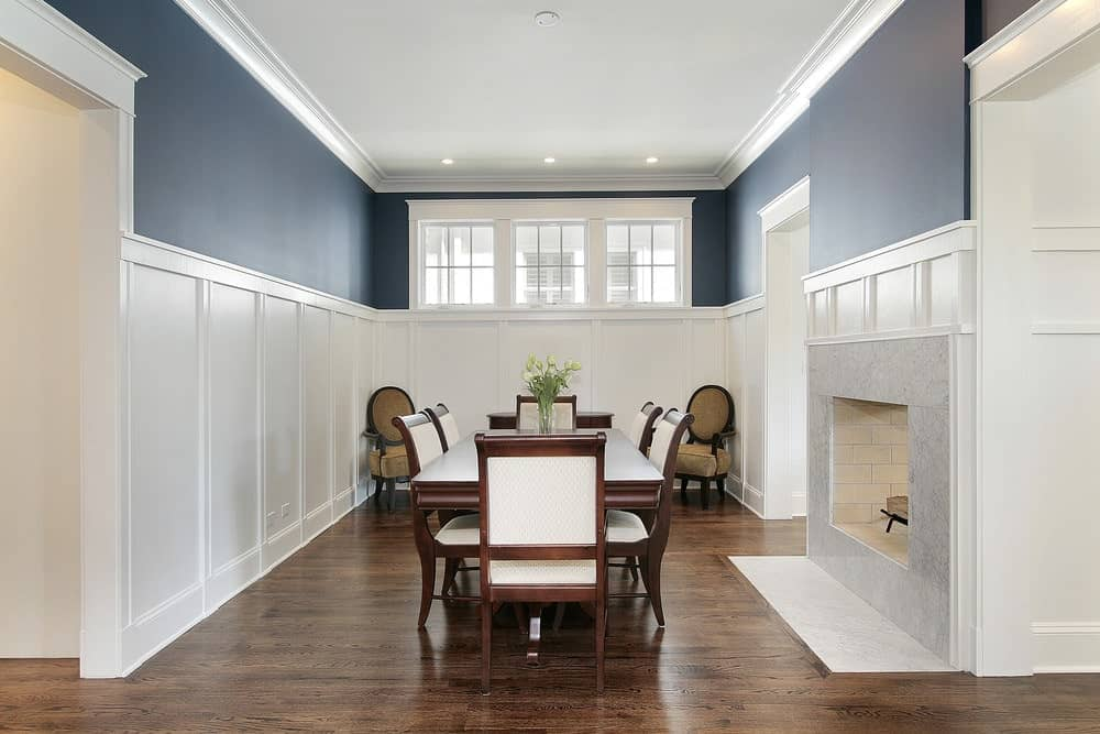The craftsmanship of the wall finishes brings a certain elegance to this narrow room. This is augmented by the brilliant bluish color of the upper walls broken by high French windows. The centerpiece is the marble fireplace next to the dark wood table and chairs.