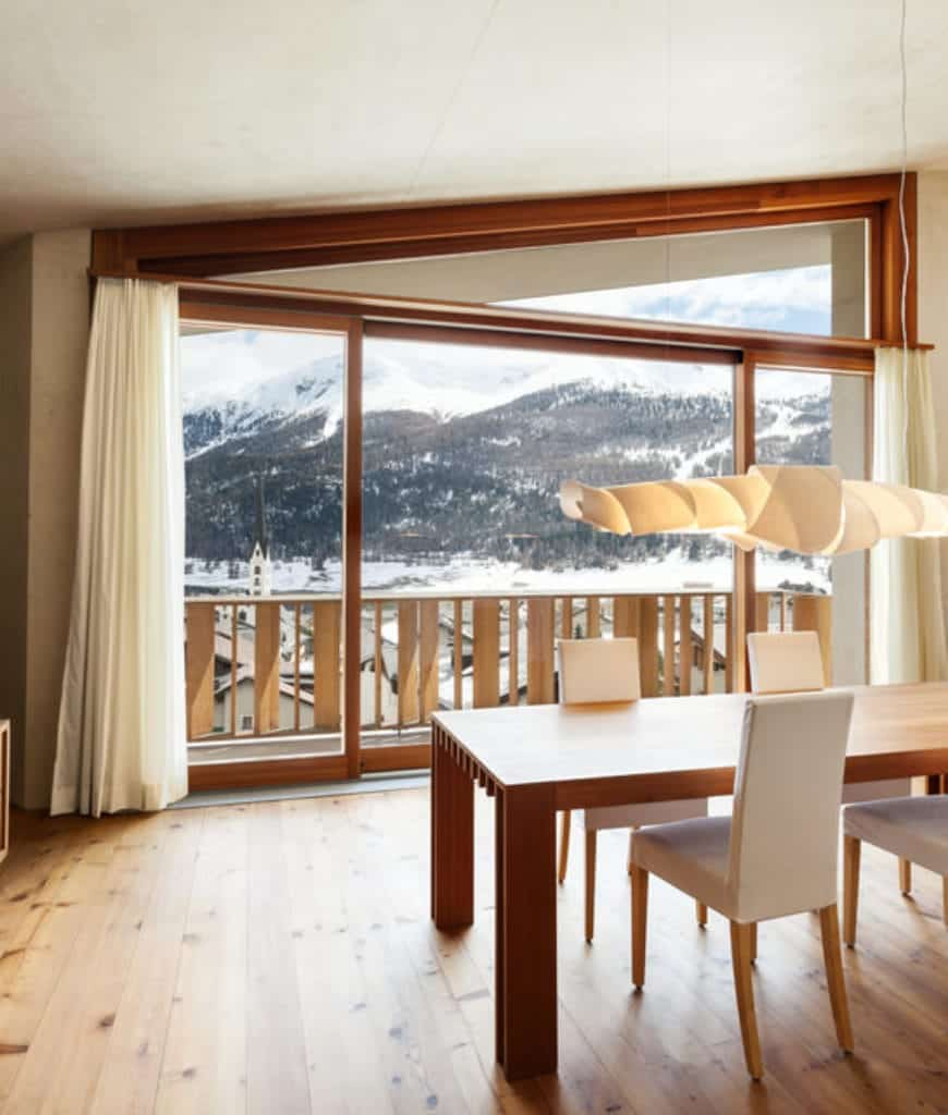 The mountain view is maximized by the floor-to-ceiling glass door that illuminates the wooden table and flooring and makes the white cushions of the chairs pop out. A peculiar hanging light hangs from the shed ceiling and it also serves as an artwork decor.