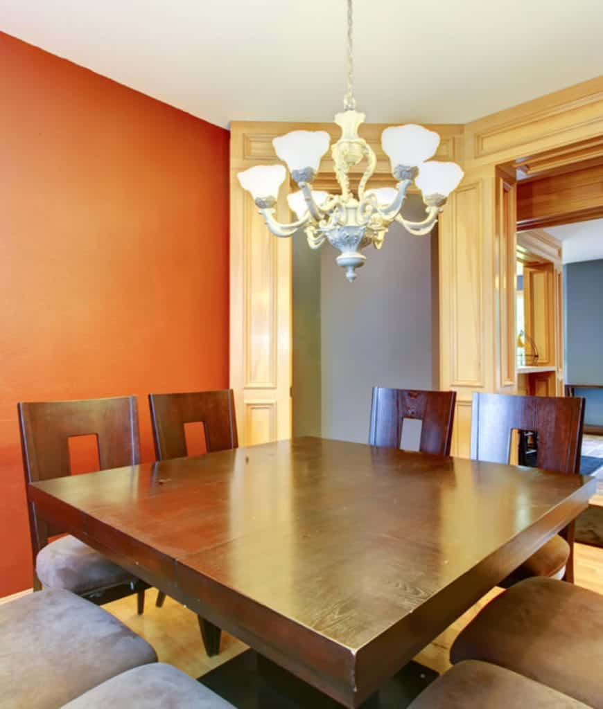The elegant white chandelier has intricate designs that contrast the simplicity of the square wooden dining table and the wooden chairs that encircle it. A simple red wall contrasts the patterned wooden finish of the doorway in this Craftsman-Style dining room.