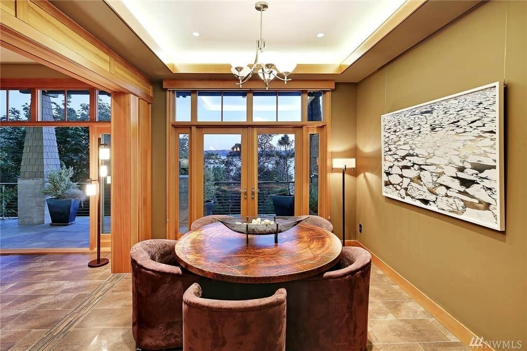 A brilliant tray ceiling illuminates this Craftsman-Style dining room with a white light that is neutralized by the brown hues of the round wooden table surrounded by comfortable velvet chairs. The wall-mounted artwork enhances the warmth of the beige walls and marble floor.