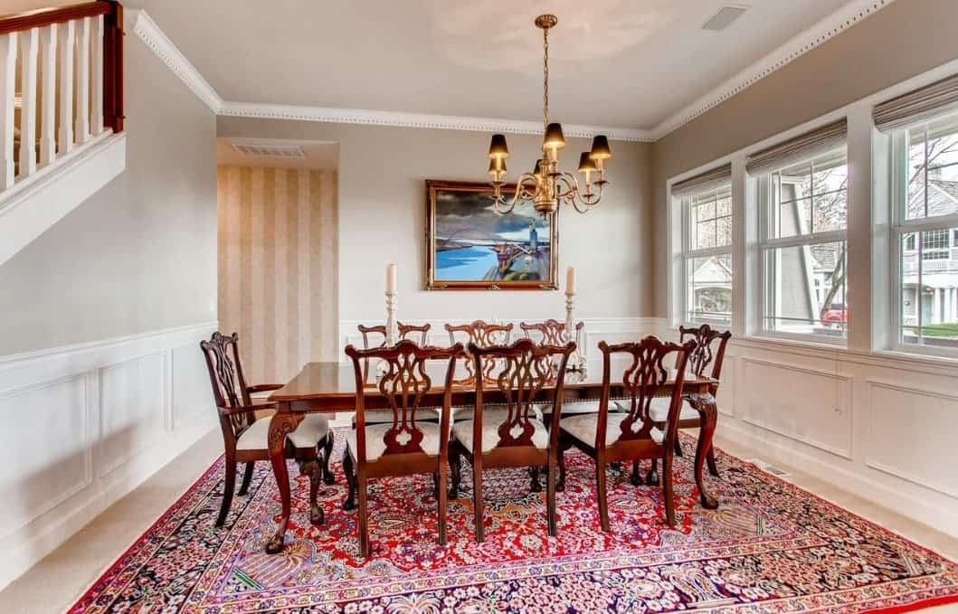 A colorful patterned rug dominates the marble floor of this Craftsman-Style dining room and serves as a good contrast to the dark wood dining table surrounded by Sheraton-backed chairs. The elegant chandelier complements the white walls and ceiling.