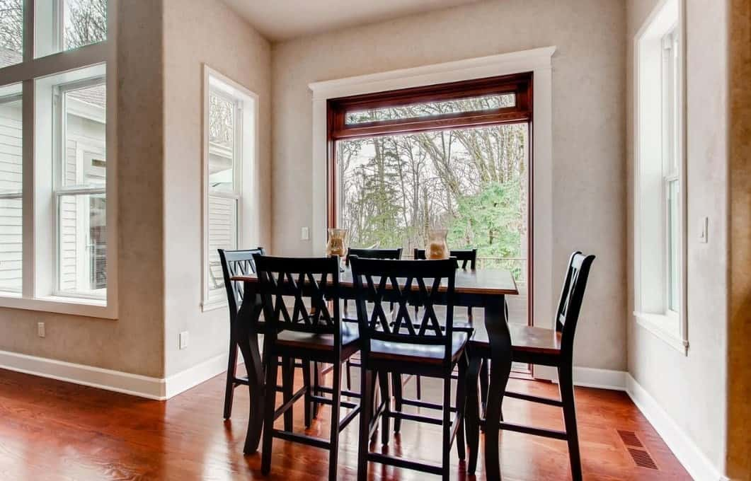 This is an intimate dining room that is given an illusion of being airy with the glass doors beside it giving a fantastic view of the woods outside. The dark wood hue of the dining table and chairs matches well with the hardwood flooring that contrast the brightness of the area.