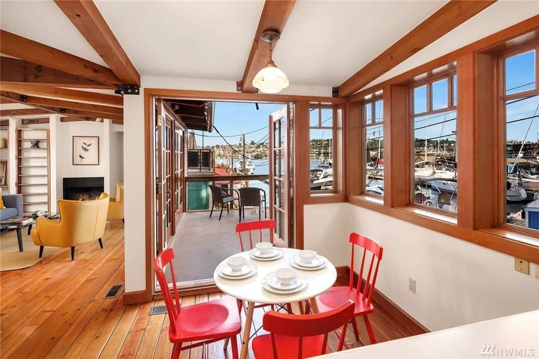 This informal dining room has wooden slat-backed chairs with a dramatic red hue that contradicts with the small white round table and white walls. The ceiling has wooden exposed beams that mirror the hardwood flooring and the frame of the windows and glass door surrounding the dining area.