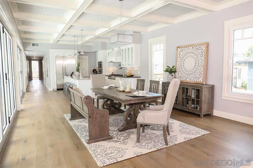 The white coffered ceiling of this Craftsman-Style dining room holds a modern pendant light that matches with the patterned rug over the hardwood floor and the framed artwork on a small cabinet. This cabinet has the same wooden finish as the dining table, chairs, and bench.