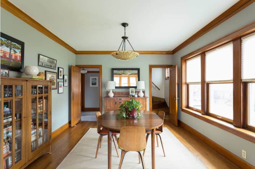 This is a simple yet elegant Craftsman-Style dining room with hardwood flooring that is paired with a white area rug. It gives a healthy contrast to the simple wooden table and chairs. The hardwood floor seems to blend into the frames of the windows that light up the room along with the peculiar pendant light.