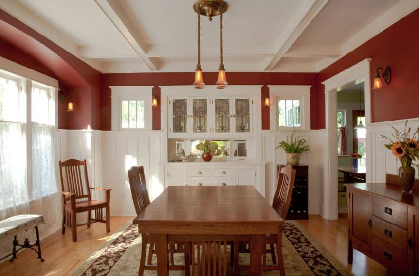 The reddish hue of the upper walls makes the white coffered ceiling seem brighter making the pendant lights pop out. The brilliant white windows and the built-in cabinet lighten up the wooden hues of the table and chairs as well as the hardwood floors with a patterned rug.