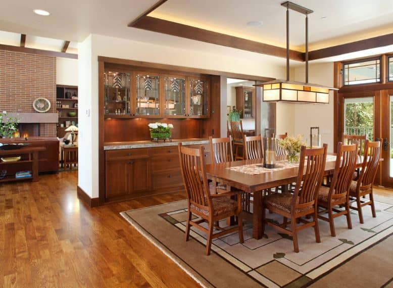 The white tray ceiling supports the peculiar house-shaped light that hangs over the rectangular wooden table surrounded by slat-backed chairs. Contrasting this is the colorful patterned rug that is placed over the hardwood floor.
