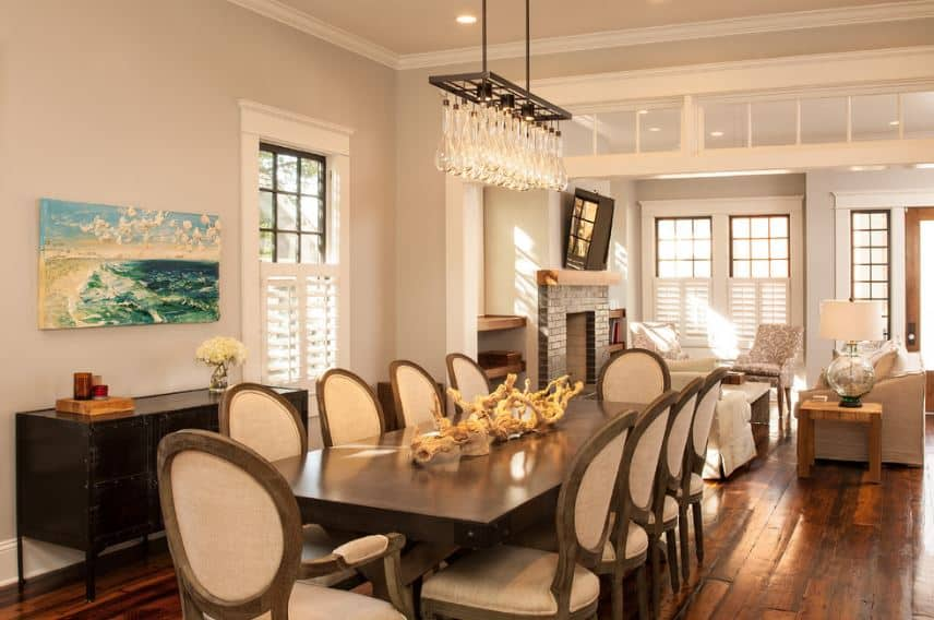 Chic dining chairs encircle the rectangular wooden table in this Craftsman-Style dining room. The dark wooden table matches the console table and hardwood floor. On the other hand, the white walls match with the white ceiling and modern chandelier.