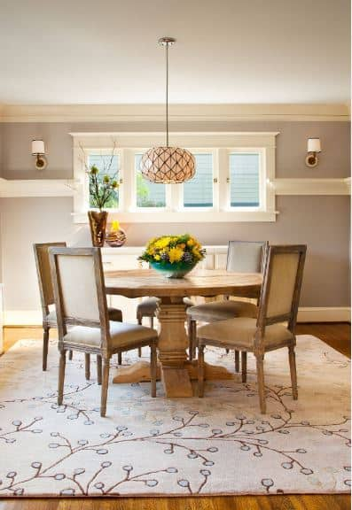 Lovely nature patterns adorn the whitish area rug over the hardwood floor of this Craftsman-Style dining room. The wooden circular table matches well with the cushioned chairs surrounding it that is illuminated by the patterned hanging light.