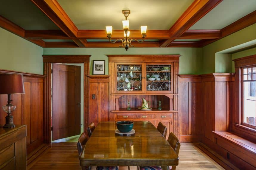 The elegant wooden hues of this Craftsman-Style dining room serve to elevate the dining experience. This is augmented by the warm light coming from the chandelier hanging from the coffered ceiling that has a greenish tinge that blend into the walls.