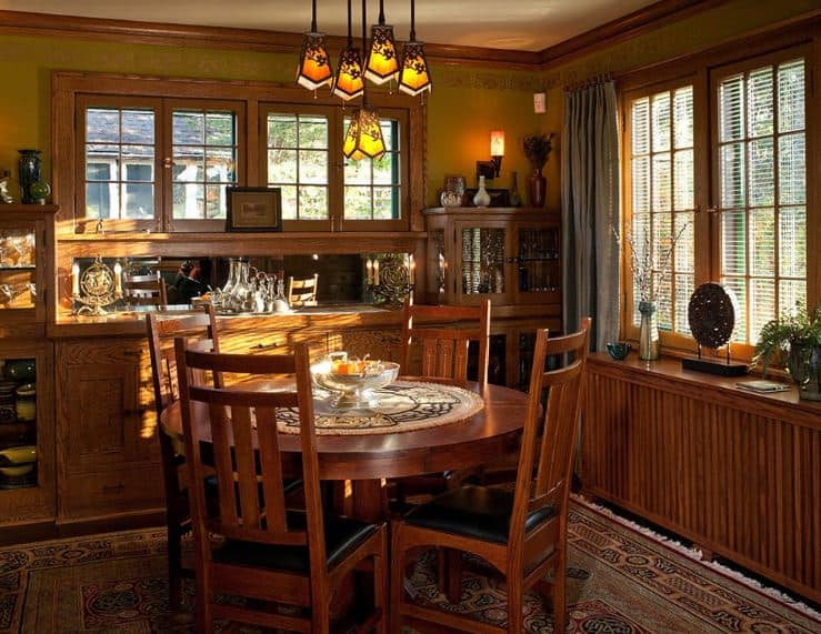 A simple Craftsman-Style dining room that has a colorful patterned rug beneath the dark wood dining table that is paired well with the dining chairs with a simple design. This mirrors the simplicity and intimate quality of the dining room that is capped off with brilliant patterned pendant lights.