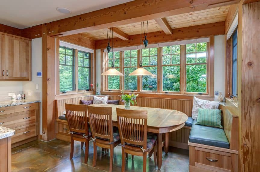 This Craftsman-Style dining room has an alcove area utilized for sitting that is surrounded by windows with a wooden finish that extends to a wooden ceiling with exposed beams. From the ceiling hangs a pair of pendant lights that illuminate the wooden table with curved edges.
