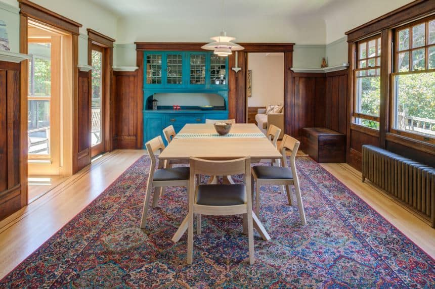 The colorful patterned area rug over the light wooden flooring catches the attention in this Craftsman-Style dining area. It is paired with light blue cabinet built-in cabinet that stands out against the dark wooden walls. The light wooden hue of the dining table and chairs are perfectly paired with the white ceiling where a pendant light hangs.