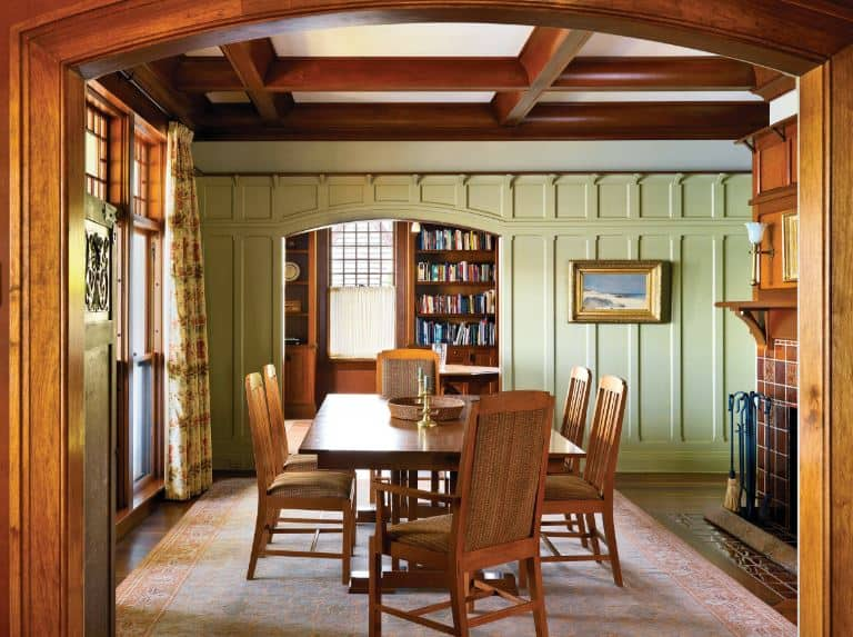 The gorgeous wooden chairs with woven wicker-like cushions surround the dark wooden table that mirrors the dark wooden exposed beams of the ceiling. Against this dark wooden hue, the light green hues of the wall stand out as well as the light hue of the area rug over the hardwood flooring.