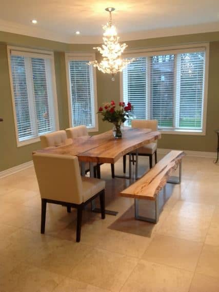 The stand-out element of this Craftsman-Style dining room is the brilliant multi-layered chandelier that emphasizes the white ceiling. The marble floor matches well with the leather chairs surrounding the wooden table and bench. This is capped off with greenish walls that bear tall windows.