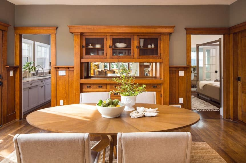 A wooden round table stands in the middle of this Craftsman-Style dining room. It is encircled by comfortable cushioned chairs that matches the white ceiling. The gray walls are accented with a wooden cabinet and finish that extends to the hardwood flooring.