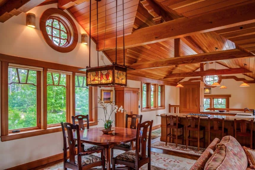This Craftsman-Style dining room has a cottage feel to it with its wooden cathedral ceilings that have exposed beams. These are paired with windows that are framed with wood against the white walls. A lovely pendant lighting with stained glass designs hangs over the wooden table and fiddleback chairs.