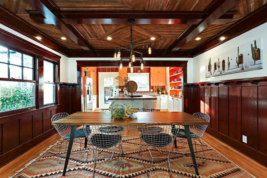 This is a Craftsman-Style dining room with Southwestern influences in its colorful patterned area rug over the hardwood flooring and the patterns of the wooden ceiling. The exposed wooden beams of the ceiling is paired well with the wall finish and window frame. This makes the wooden table and metallic chairs stand out.