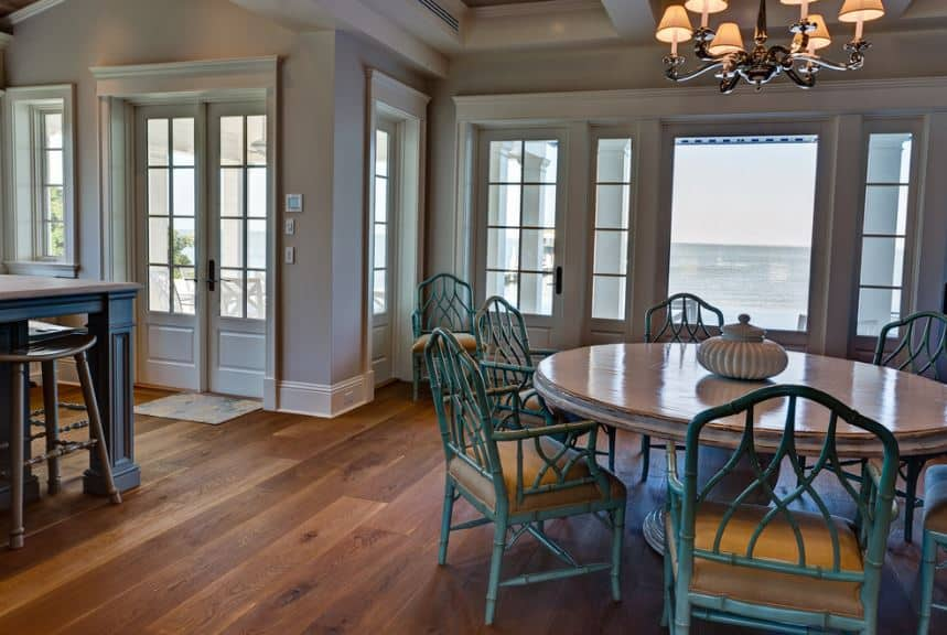 The charming wooden chairs in this Craftsman-Style dining room has intricate designs and are painted with a bluish hue that makes them stand out against the hardwood flooring and white walls that match the wooden round table. A touch of elegance comes from the chandelier hanging from the coffered ceiling.