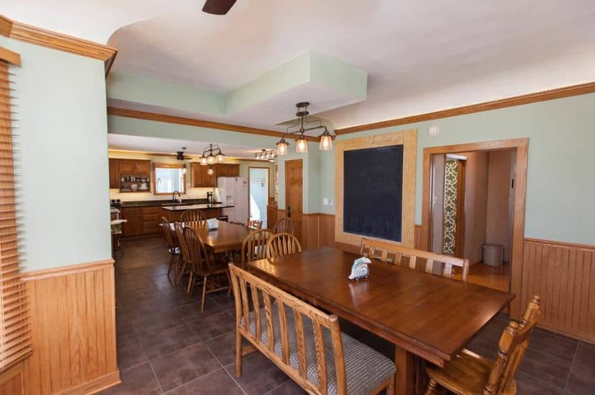 This is a Craftsman-Style dining room that can clearly cater to a large family with its two wooden tables surrounded by slat-backed chairs and a bench. They are capped by a white tray ceiling with modern chandeliers that matches the dark tiles of the flooring.