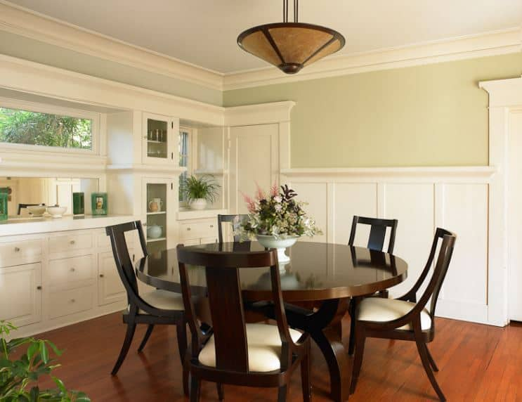 The stand out elements in this Craftsman-Style dining room are the dark wooden elements of the hardwood flooring, pendant light, round wooden table and the wooden cushioned chairs surrounding it. Balancing this are the light hues of the wall finish, built-in cabinets and white ceiling.
