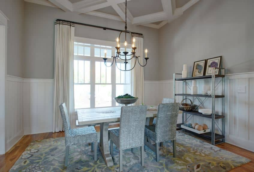 This Craftsman-Style dining room has a chic quality to it with its floral colorful area rug placed over the hardwood flooring. This is paired with woven wicker chairs that is painted with the same hue as the area rug. This pairs well with the light gray walls that extend to the coffered ceiling where a simple chandelier hangs.
