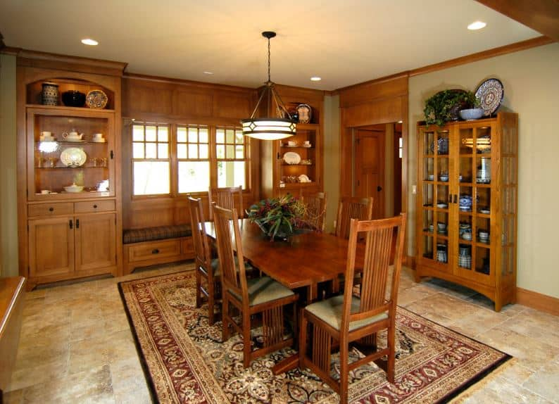 This Craftsman-Style dining room is dominated by its wooden elements. It can be seen in its wall finish paired with built-in cabinets, reading nook by the window and the wooden table that is paired with wooden chairs. The counterbalance to this is the colorful patterned area rug over the marble flooring.