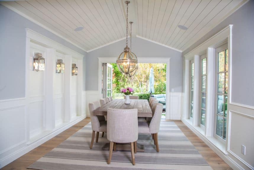 This dining room has a beach house feel to it with its high cathedral shiplap ceiling and the light gray hues of the wall that blends with the striped area rug over the hardwood flooring. Spherical pendant lights hang over the wooden table that is surrounded cushioned chairs.