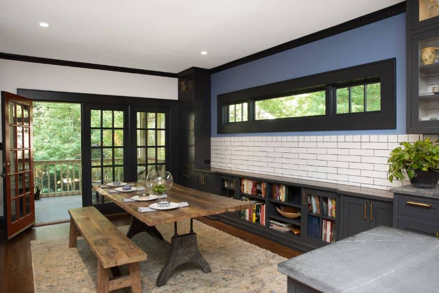 The dark gray hue of the French doors blends into the built cabinets that meld into a long counter by the wall with a white-tiled wall above it. The wooden table is paired with a long wooden bench, giving it an outdoor picnic quality. This is paired with a beige rug over dark wooden flooring.