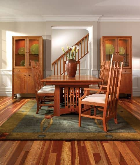 A colorful patterned rug is placed over the hardwood flooring of this Craftsman-Style dining room. The green hue of this rug is reflected onto the decorative plates in the wooden cabinets flanking the entryway. The lovely wooden dining table and cushioned chairs match with the other wooden hues of the room.