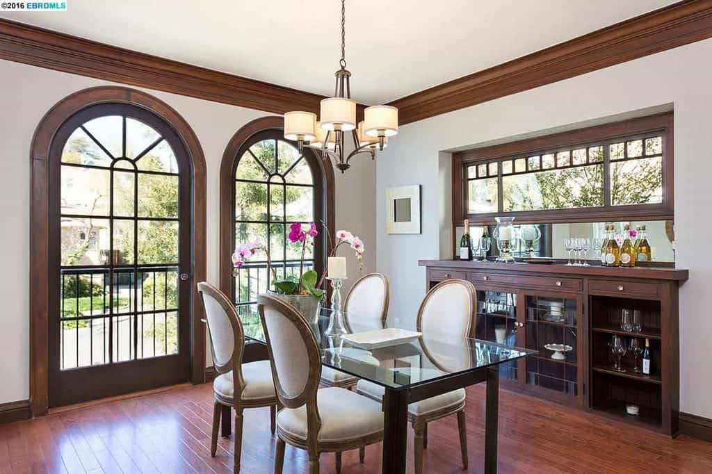 Glass French doors with an arched top provide illumination to the glass-top table with white cushioned chairs. The frames of the doors match the ceiling moldings and a built-in cabinet beneath a rectangular window across the modern chandelier.