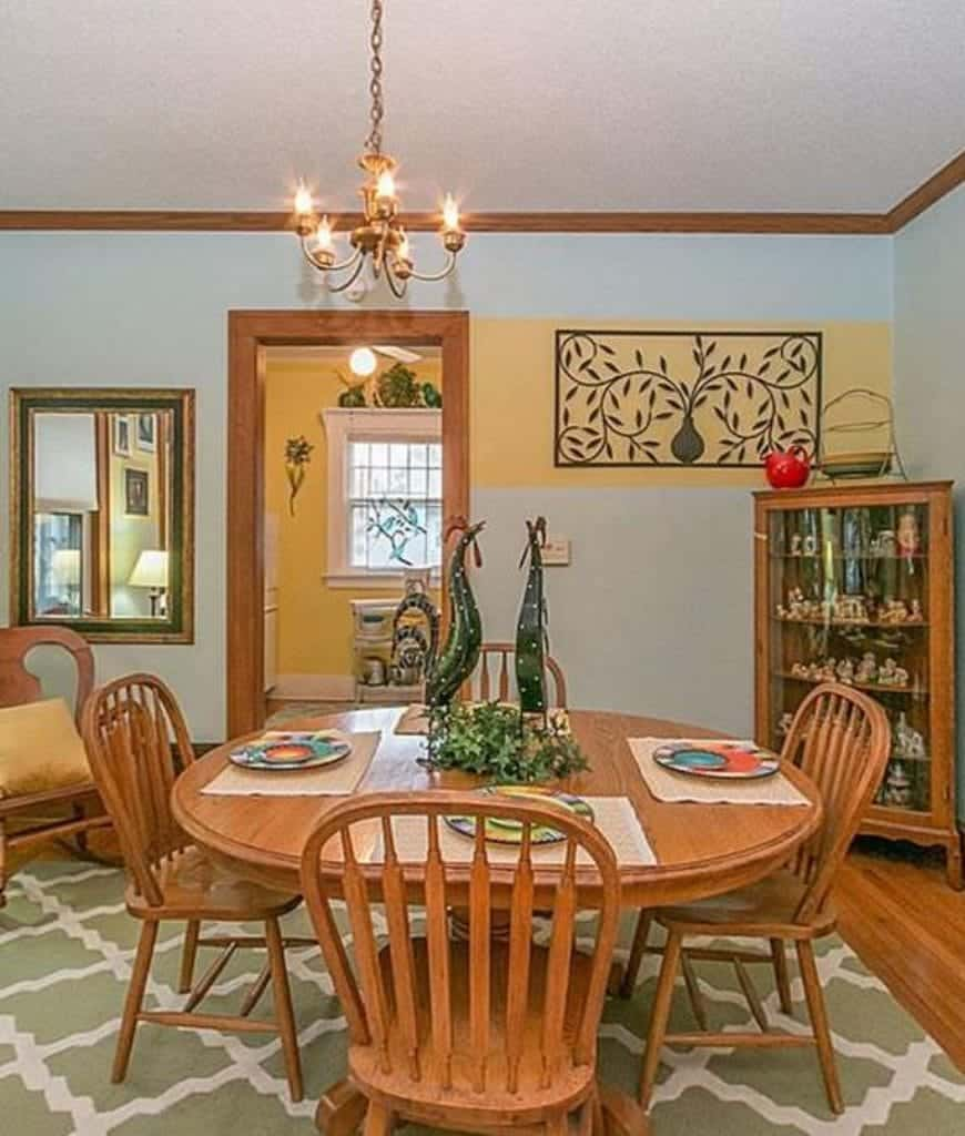 A charming green patterned area rug is placed over the hardwood floor that matches the wooden round table and slat-backed chairs. A small scale chandelier hangs from the white ceiling that makes the table-top centerpiece stand out.