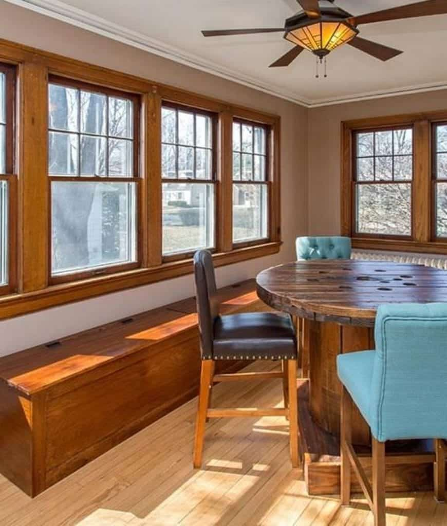 The rustic wooden circular table seems like a recycled cable reel that caps off the wooden charm of this Craftsman-Style dining room. The wooden frames of the windows reflect on the long bench beneath the windows and the upholstered chairs.