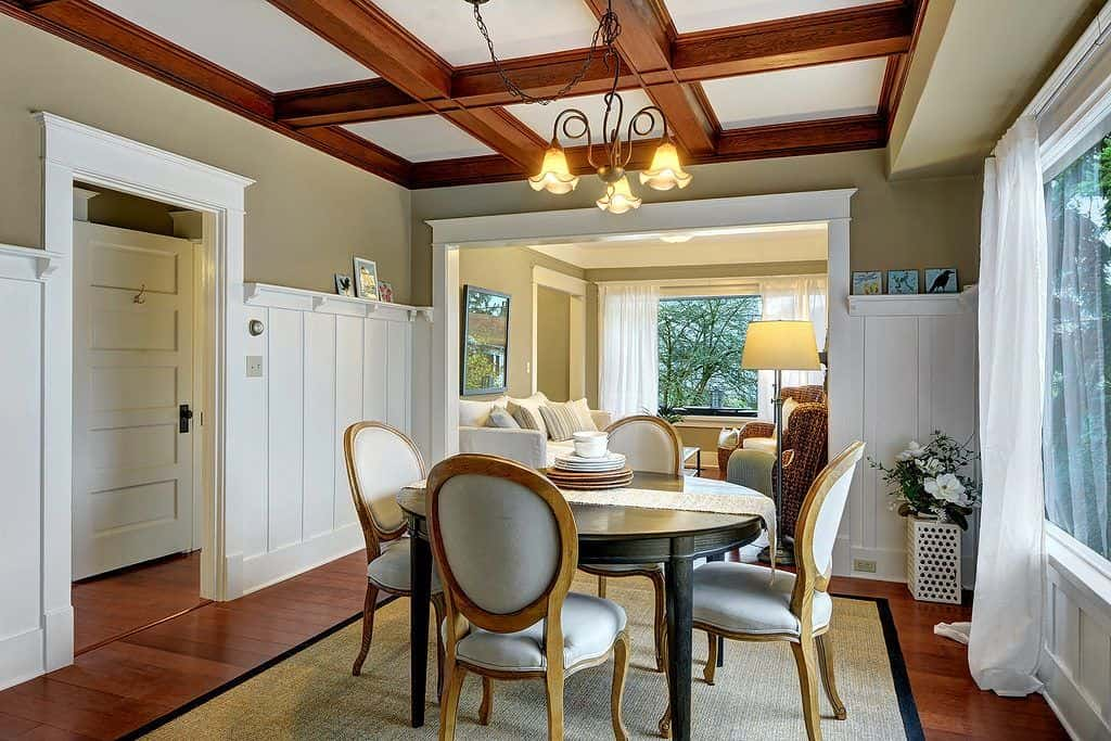 This Craftsman-Style dining room has a coffered ceiling that supports the charming curvy chandelier that hangs over the dar wooden circular table. This is surrounded by four chic dining chairs with leather upholstery that matches the white walls.