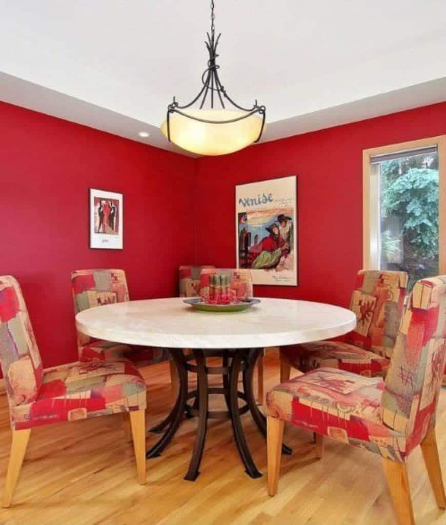 Vibrant red hues dominate this Craftsman-Style dining room with its stark red colors and red-patterned cushions of the dining chairs encircling the white round table with dark iron legs. Vintage wall-mounted artworks pop out against the red walls and white ceiling.
