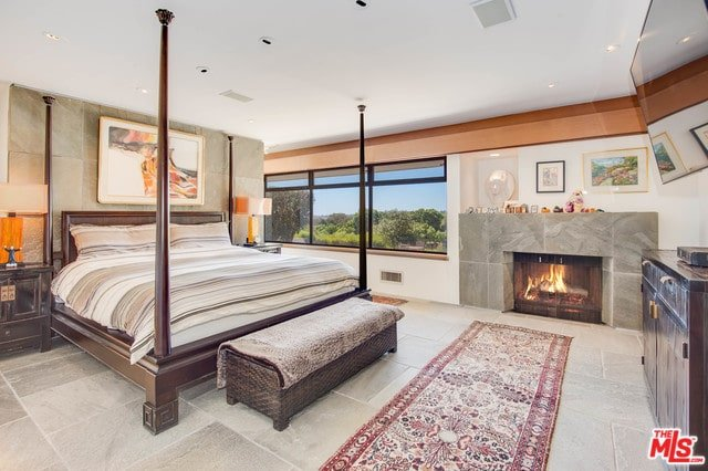 This primary bedroom features a four-poster bed with a wicker bench on its end along with a red runner that lays on the concrete tiled flooring extending to the fireplace surround and bed's backdrop.
