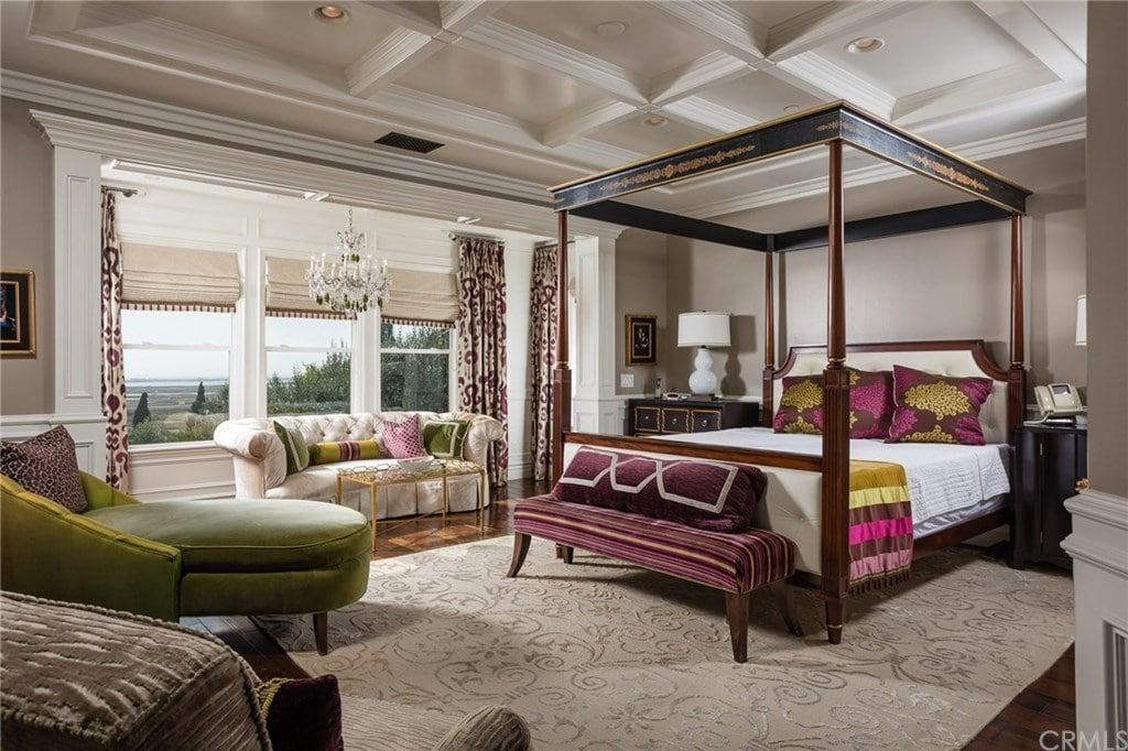 Large primary bedroom with coffered ceiling and hardwood flooring topped by a floral textured rug. It is furnished with various styled seats and a canopy bed flanked by dark wood nightstands against the white wainscoting.