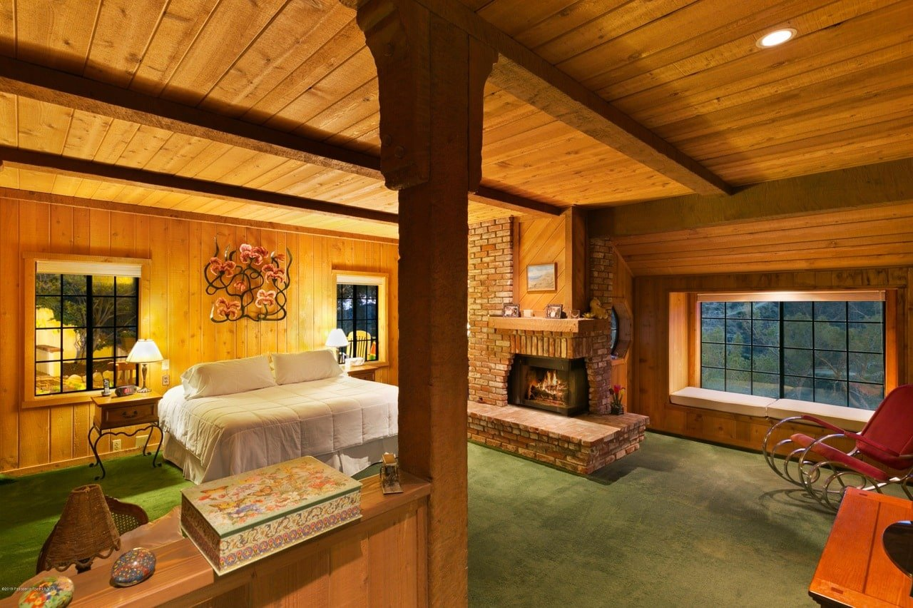 Ambient light from the table lamps and brick fireplace creates a warm and cozy feel in this primary bedroom with green carpet flooring and wood plank walls extending to the wood beam ceiling.