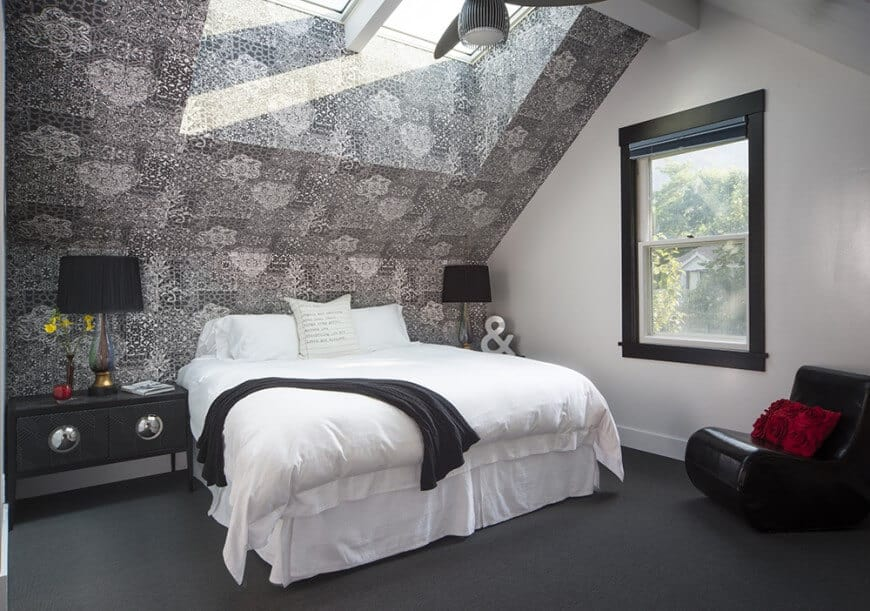 Primary bedroom boasting a stylish gray wall and ceiling, along with dark gray carpet flooring. The room offers a white bed along with black bedside tables topped by black table lamps.