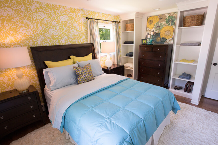 A focused shot at this primary bedroom's charming bed setup. The room features elegant yellow walls and two bedside tables, along with built-in shelving.