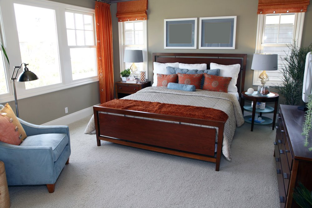 Primary bedroom featuring gray carpet flooring and gray walls. It offers a classy bed setup lighted by gray table lamps on top of bedside tables.